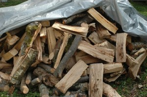 A pile of fire wood on the ground covered in a tarp