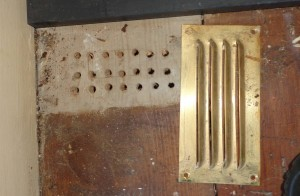 A vent removed to reveal small drilled holes behind